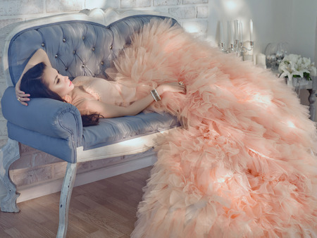 Fashionable portrait of beautiful lady in gorgeous couture dress on sofa