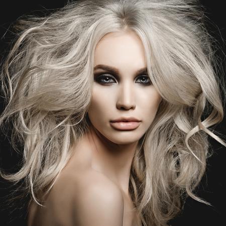 smoky black: Fashion studio portrait of beautiful blonde woman with volume hairstyle on black background Stock Photo