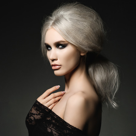 woman hairstyle: Fashion studio portrait of beautiful blonde woman with elegant hairstyle on black background