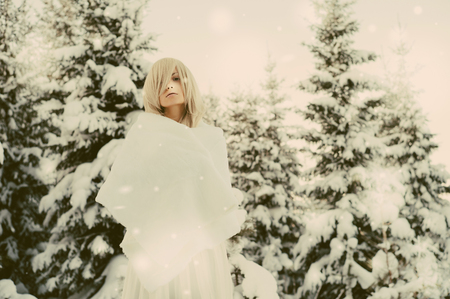 beautiful weather: Outdoor atmospheric fashion photo of young beautiful lady in winter forest. Fur coat. Cold weather. Snowflakes