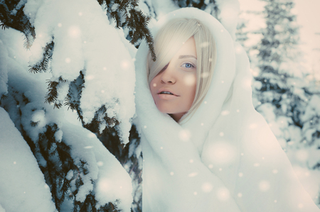 winter weather: Outdoor atmospheric fashion photo of young beautiful lady in winter forest. Fur coat. Cold weather. Snowflakes