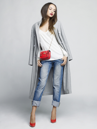 Fashion studio foto van de jonge modieuze vrouw. Grijs oversized jas, wit shirt, blauwe spijkerbroek, rode schoenen en handtas. Catalogus kleding. Kijkboek Stockfoto