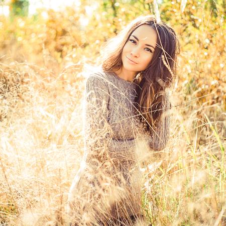 Outdoor atmospheric fashion photo of young beautiful lady. Autumn field. Autumn lanscape. Warm autumn. Warm spring Stock Photo