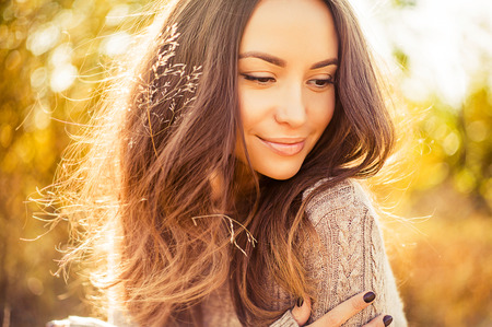 Outdoor atmospheric lifestyle photo of young beautiful lady. Brown hair and eyes. Warm autumn. Warm spring Archivio Fotografico