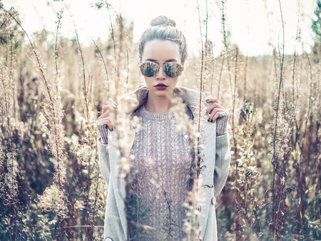 Outdoor fashion photo of young beautiful lady in autumn landscape with dry flowers. Knitted sweater, sunglusses, wine lipstick. Warm Autumn. Warm Spring