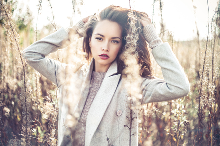 long: Outdoor fashion photo of young beautiful lady in autumn landscape with dry flowers