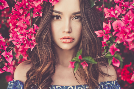 Outdoor fashion photo of beautiful young woman surrounded by flowers. Spring blossom Imagens - 74897738