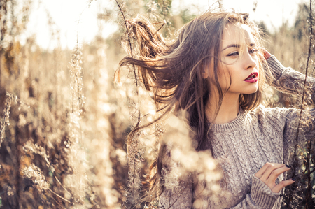 photo: Outdoor fashion photo of young beautiful lady in autumn landscape with dry flowers. Knitted sweater, wine lipstick. Warm Autumn. Warm Spring Stock Photo