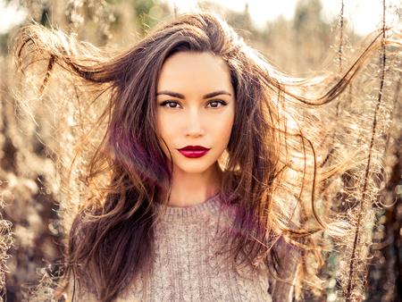 마른 꽃 가을 풍경에서 젊은 아름 다운 여자의 야외 패션 사진. 니트 스웨터, 와인 립스틱. 따뜻한가. 따뜻한 봄