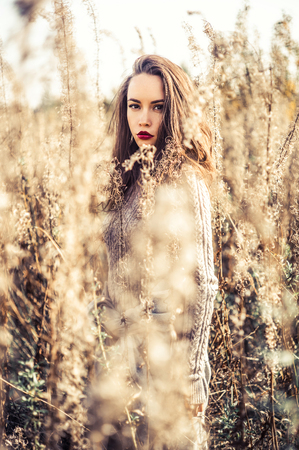 long: Outdoor fashion photo of young beautiful lady in autumn landscape with dry flowers. Knitted sweater, wine lipstick. Warm Autumn. Warm Spring Stock Photo