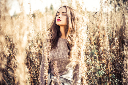 Outdoor fashion photo of young beautiful lady in autumn landscape with dry flowers. Knitted sweater, wine lipstick. Warm Autumn. Warm Spring Stok Fotoğraf