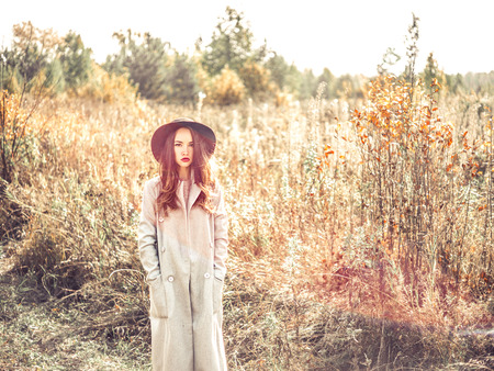 Outdoor fashion photo of young beautiful lady in autumn landscape with dry flowers. Gray coat, black hat, wine lipstick. Warm Autumn. Warm Spring