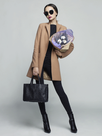 fashion clothes: Fashion studio photo of young stylish woman. Beige coat, black leather boots and bag, bouquet of lavender. Catalogue clothes. Lookbook Stock Photo