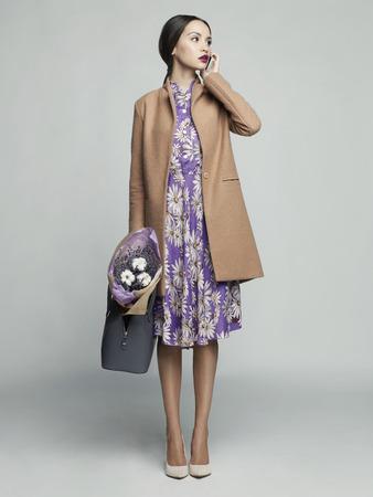 Fashion Studio Foto von jungen stilvollen Frau. Beige Mantel, Bouquet von Lavendel. Katalogkleidung Lookbook Standard-Bild - 75070353