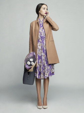 Fashion studio photo of young stylish woman. Beige coat, bouquet of lavender. Catalogue clothes. Lookbook