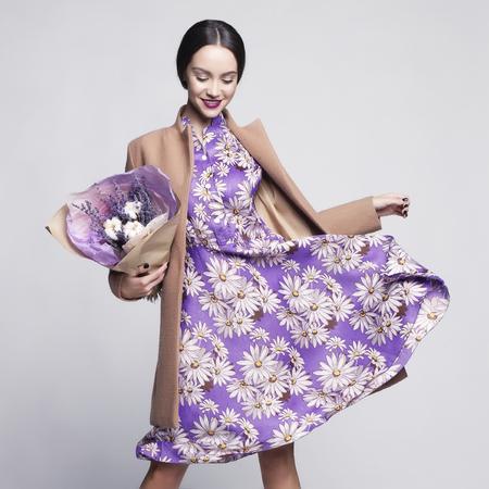 Fashion studio foto van jonge stijlvolle vrouw. Beige jas, lila jurk, boeket lavendel. Cataloguskleding en accessoires. Kijkboek