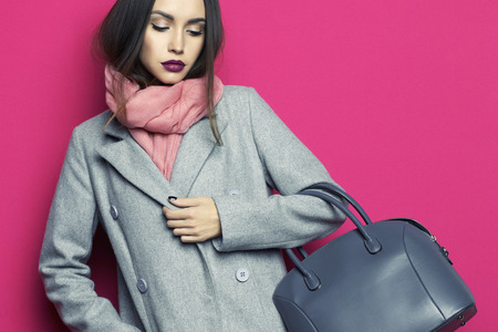 hair and beauty: Fashion studio photo of young stylish woman on fuchsia background. Gray coat, pink scarf, purple lipstick, leather bag, . Catalogue clothes and accessories. Lookbook