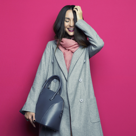 Fashion studio photo of young stylish woman on fuchsia background. Gray coat, pink scarf, purple lipstick, leather bag, . Catalogue clothes and accessories. Lookbook