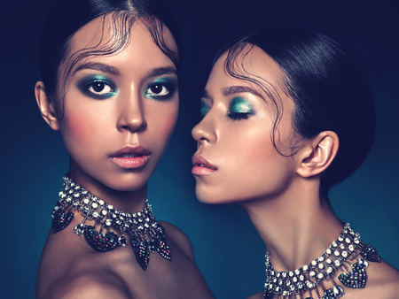 Fashion studio portrait of two twins beautiful asian women with diamond necklace. Fashion and Beauty. Perfect makeup