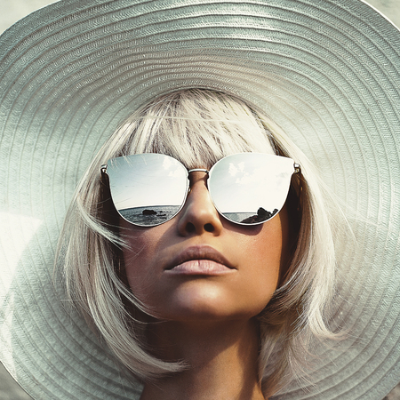 Outdoor fashion photo of young beautiful lady in hat and sunglasses. Summer Beach travel. Summer vibes Standard-Bild