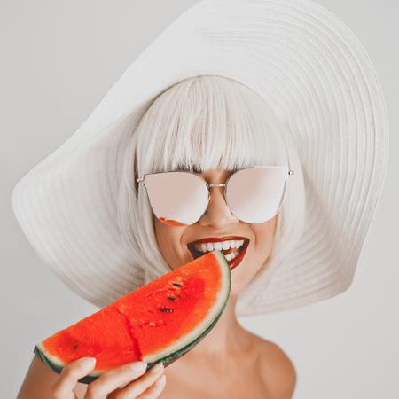 アウトドアファッション帽子とサングラスにスイカの若い美しい女性の写真。夏のビーチの旅行。夏の感じ 写真素材