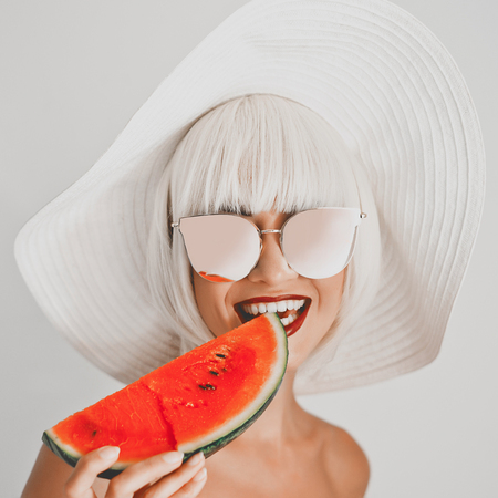 Outdoor fashion photo of young beautiful lady in hat and sunglasses with watermelon. Summer Beach travel. Summer vibes