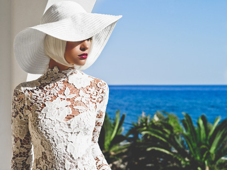 Outdoor fashion photo of young beautiful lady in white hat at sea. Summer Beach travel. Summer vibes Stock Photo