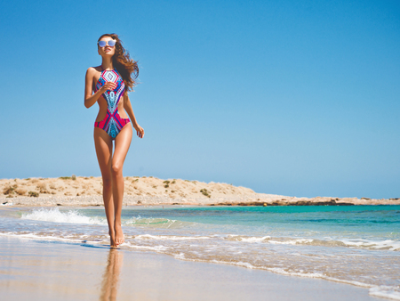 Outdoor fashion photo of beautiful happy slender woman running on sea. Beach travel. Summer vibes Stock Photo