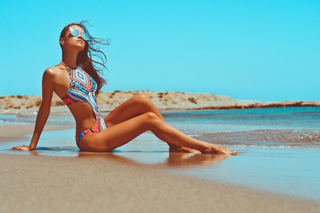 swimsuite: Outdoor fashion photo of beautiful happy slender woman sitting at sea. Beach travel. Summer vibes Stock Photo