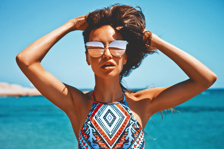 Outdoor fashion photo of beautiful happy woman at sea. Beach travel. Summer vibes photo