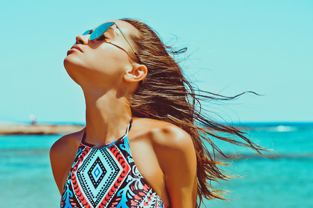 Outdoor fashion photo of beautiful happy woman at sea. Beach travel. Summer vibes Standard-Bild