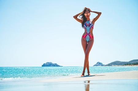 海で幸せなスレンダー美女の屋外ファッション写真。ビーチ旅行。夏の感じ