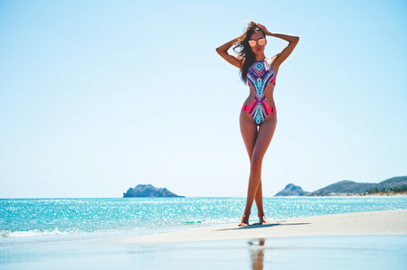 Outdoor fashion photo of beautiful happy slender woman at sea. Beach travel. Summer vibes photo