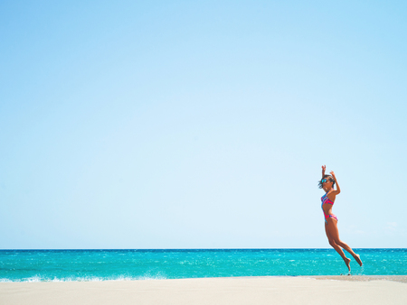 Outdoor fashion photo of beautiful happy slender woman jumping on sea. Beach travel. Summer vibes