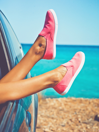 Outdoor photo of female legs from the window of car. Freedom, summer travel and road trip Standard-Bild