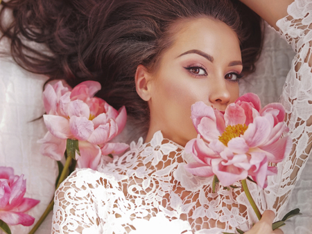 Stilvolles Modefoto der schönen jungen Frau liegt unter Pfingstrosen. Feiertage und Ereignisse. Valentinstag. Frühlingsblüte. Sommersaison Standard-Bild