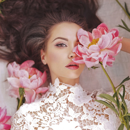 Stylish fashion photo of beautiful young woman lies among peonies. Holidays and Events. Valentines Day. Spring blossom. Summer season