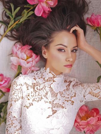 Stijlvolle mode foto van mooie jonge vrouw ligt tussen pioenrozen. Feestdagen en evenementen. Valentijnsdag. Lente bloesem. Zomerseizoen