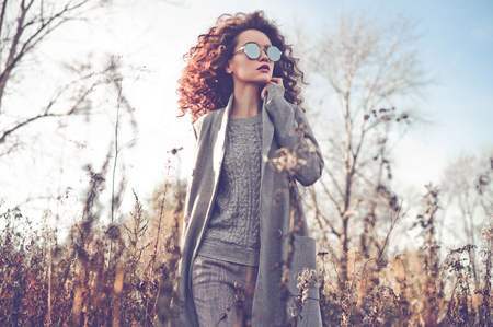 Outdoor fashion photo of young beautiful lady in autumn landscape with dry flowers. Gray coat, knitted sweater, sunglasses, wine lipstick. Fashion lookbook. Warm Autumn. Warm Spring