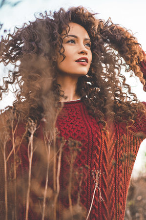 Outdoor lifestyle fashion photo of young natural beautiful lady in autumn landscape with dry flowers. Knitted sweater, wine lipstick. Warm Autumn. Fall vibes