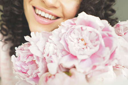 Lifestyle photo of beautiful smiling woman with pink peonies. Bouquet as gift. Emotions of happiness and joy