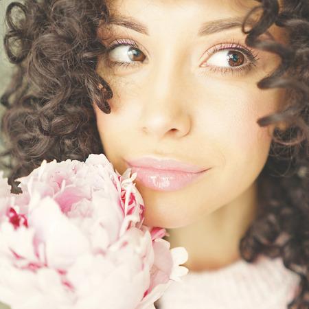 분홍색 모란와 아름 다운 미소 여자의 라이프 스타일 사진. 선물로 꽃다발. 행복과 기쁨의 감정