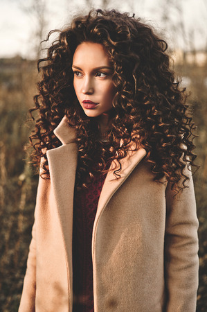 Outdoor fashion photo of young beautiful lady in autumn landscape. Beige coat, knitted sweater, wine lipstick. Fashion lookbook. Warm Autumn. Warm Spring