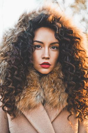 Openluchtmanierfoto van jonge mooie dame in de herfstlandschap. Beige jas, bontkraag, wijnlippenstift. Mode lookbook. Warme herfst. Warme winter