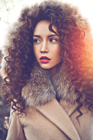Outdoor fashion photo of young beautiful lady in autumn landscape. Beige coat, fur collar, wine lipstick. Fashion lookbook. Warm Autumn. Warm winter Stock Photo