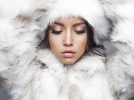 Fashion studio portrait of beautiful lady in white fur coat and fur hat. Winter beauty in luxury. Fashion fur. Beautiful woman in luxury fur coat. Fashion model posing in eco-fur coat and eco-fur hat