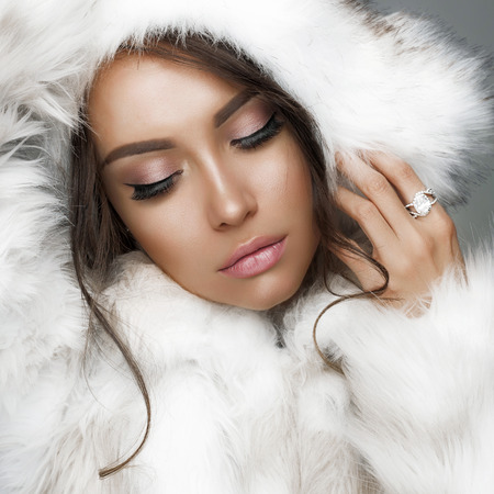 Fashion studio portrait of beautiful lady in white fur coat and fur hat. Winter beauty in luxury. Fashion fur. Beautiful woman in luxury fur coat. Fashion model posing in eco-fur coat and eco-fur hat 스톡 콘텐츠