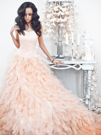 Fashionable portrait of beautiful lady in gorgeous couture dress in white interior. Holidays & Events. Evening dress