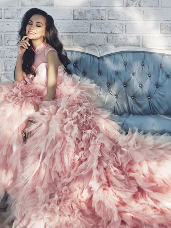 Fashionable portrait of beautiful lady in gorgeous couture dress on sofa. Holidays & Events. Evening dress. Princess dress. Christmas and New Year Banque d'images