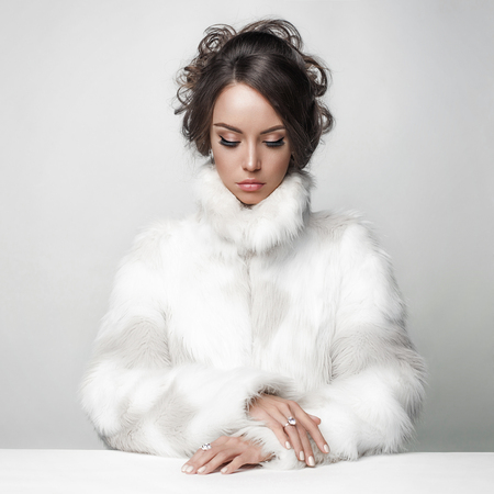Fashion studio portrait of beautiful lady with elegant hairstyle in white fur coat. Winter beauty in luxury. Fashion fur. Beautiful woman in luxury fur coat. Fashion model posing in eco-fur coat